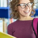 Woman in library big smile holding a book