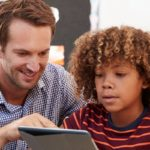 Teaching assistant help boy with i pad