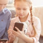 two children looking at a smartphone screen